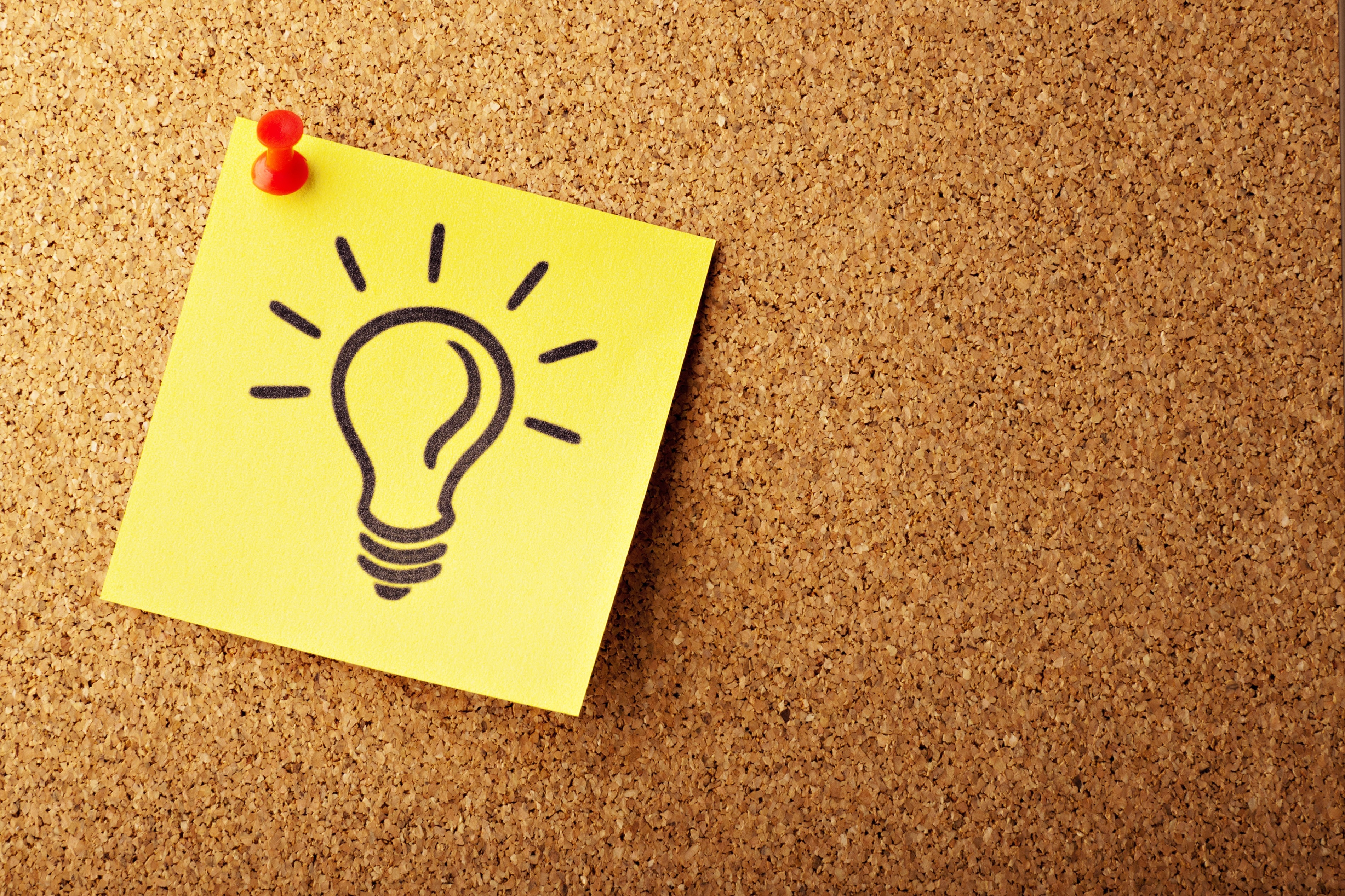 A cork pin board with a yellow postit note on which is drawn a light bulb