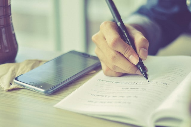 Close up image of a desk with a smart phone and a hand holding a pen writing in a notebook